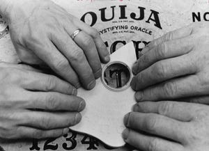 Ouija board users rest their fingers on a planchette while waiting for spelled-out messages from the great beyond.