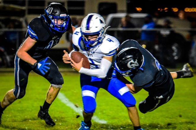 Collins-Maxwell quarterback Jace Huntrods tries to escape the grip of Colo-NESCO's Nolan Smith (40) and Lucas Frohwein as Smith and Frohwein bring him down for a sack during the Spartans' 40-14 loss to the Royals Friday at Colo.