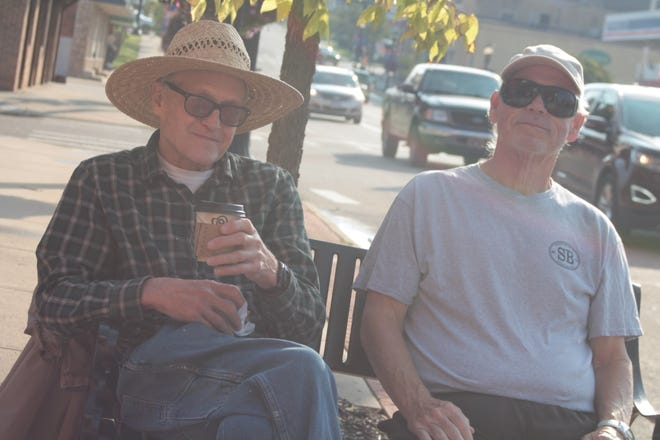 Carl Brazell Jr. owner of Club Billiards and a regular at Ladders Coffee Bar, enjoys a cup of coffee on an outside bench with friend Les Wojciechowski.