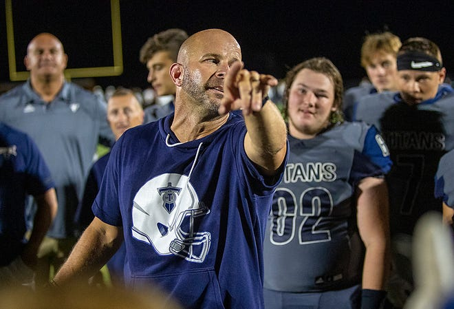 Monmouth-Roseville High School football coach Jeremy Adolphson talks to his team after the Titans beat Spring Valley Hall 40-32 on Saturday, Sept. 4, at Coach Dobry Field.