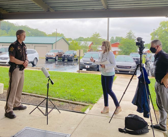 """Anne Marie Tiernan from WTHR-TV interviews Brown County Sheriff Scott Southerland, left, about drug use issues in Brown County, the focus of a new documentary, """"The Addict's Wake."""""""