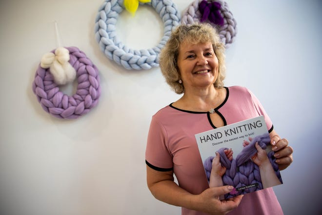 Larissa Koedyker, owner of BeCozi, holds her recently published book in her studio Tuesday, Sept. 28, 2021.