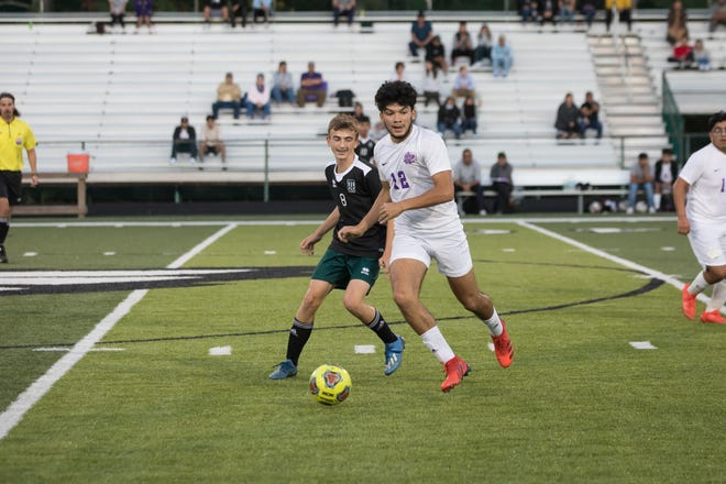 West Henderson's Rubisel Sanchez (12) and East Henderson's Daniel Lajos fight for the ball during during a match earlier this season.