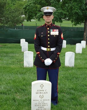 U.S. Marine Corps veteran John Morgan poses for a photo at the grave of his grandfather, a medal of honor recipient.