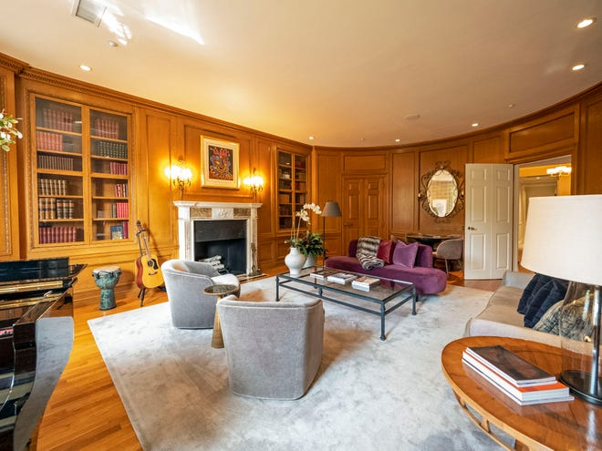 A double door connects to the oak-paneled library, where a concave wall with curved doors mirrors the bowfront and ceiling-height bookcases foster a scholarly atmosphere.