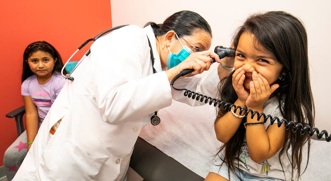 In this file photo from June 4, 2020, Emilie Sanchez, 4, right, giggles as Dr. Tess Ribay, center, tickles her ears while checking her ear canal during an exam at Heart of Florida Health Center. The nonprofit will receive funding for a pediatric dental specialist, mobile care unit and behavioral health pharmacy from the Marion County Hospital District.