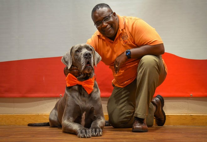 Johnnie Bryant poses with Maverick, one of the therapy animals at the Fort Leonard Wood USO.  (Photo by Amanda Sullivan, Fort Leonard Wood Public Affairs Office)