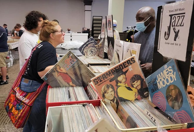 Customers talk to record vendor Bill Cox on Aug. 8, 2021, during the South Bend Record Show at the Ramada by Wyndham. The returns to the hotel on Oct. 3, 2021.