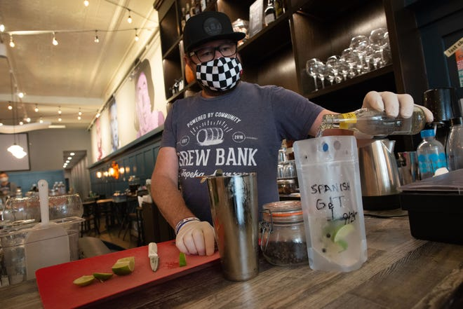 Ryan Cavanaugh, co-owner of Brew Bank, 822 S. Kansas Ave., pours in tonic water to top off a to-go version of the restaurants' Spanish Gin. Cavanaugh said adding the ability for to-go drinks has been good for his business, with custom cocktails being especially popular.