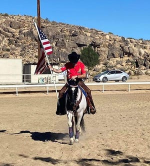 Rider Roger Gregoire carries the American Flag during the Mojave River Valley Horsemen's Association show at Horseman's Center in Apple Valley on Sept. 11, 2021.