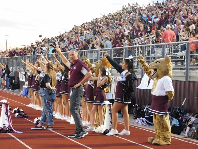 Ennis ISD athletic director Don Drake observes the scene in front of EHS cheerleaders and a packed homecoming crowd on Friday night before the game against Sulphur Springs.