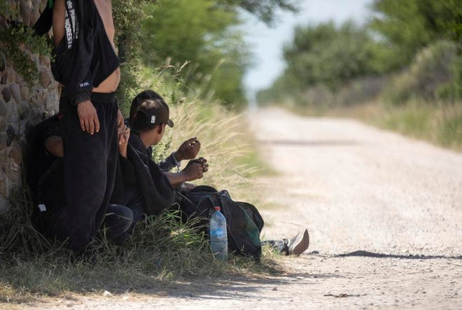 Migrants wait near a private road after being apprehended by Texas Department of Public Safety officers at a train depot in Kinney County.