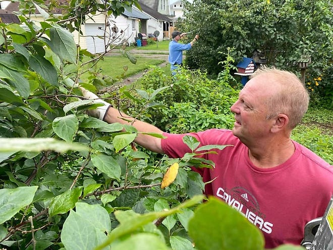 Bob Owen and Don Lightell clean up some landscaping as members of One Flowerbed at a Time.