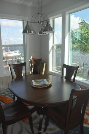 Picturesque views of the back bays, boats and bridge are seen from most rooms. This dining area features a dark wood table that forms a contrast to the light floors and walls.