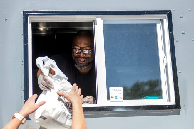 Eddie Jones, owner of Triple E's Food Truck, hands food to a customer on Tuesday, Sept. 28, 2021, at an office complex in East Lansing.