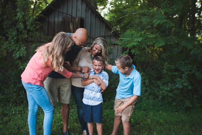 The Thornhill family surrounds son and brother Marcus Thornhill during a photo shoot before his death in 2020. At left is Hannah, now 15. At right is Isaac, 12, with parents Josh and Katie in the center.