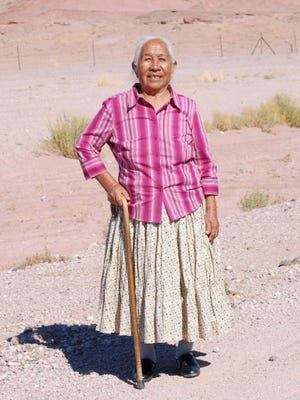 Agnes Laughter stands with her cane in the Arizona desert.