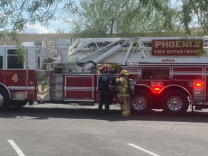 Two Phoenix firefighters prepare on scene of a possible chlorine leak at Phoenix Country Day School on Sept. 28, 2021.