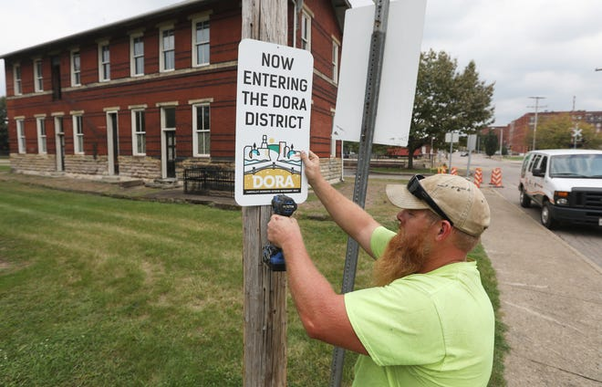 Josh Ayres of Kessler Sign Company installs the first sign marking the boundry of the DORA in Zane's Landing Park on Tuesday.