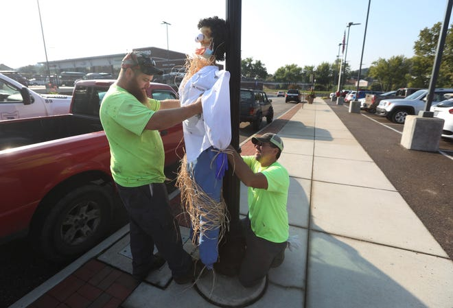 Travis Lane, left, and Lloyd Nicholson with the city of Zanesville attach a scarecrow to a lamppost on Fifth Street Tuesday morning. Fifty-six scarecrows will decorate downtown and Mission Oaks Gardens through October. The public can vote for their favorite by visiting www.visitzanesville.com. Voting begins Oct. 1. The scarecrows were made by local businesses and organizations. The $25 entry fee for the contest will benefit the Muskingum Valley Park District.
