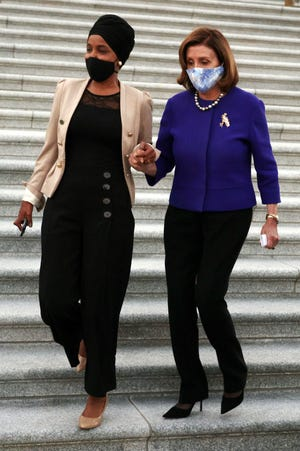 House Speaker of the HNancy Pelosi, D-Calif., (right)  and Rep. Ilhan Omar, D-Minn., (left) hold hands as they arrive at a group photo to mark the National Recovery Month outside the U.S. Capitol on Sept. 27, 2021 in Washington, D.C.