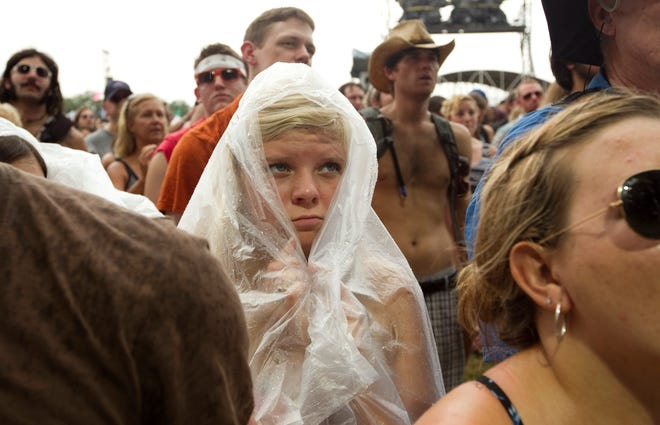 Coco Lowenfield takes cover from the rain while watching J. Roddy Walston and the Business at the Austin City Limits Music Festival on Sept. 17, 2011.