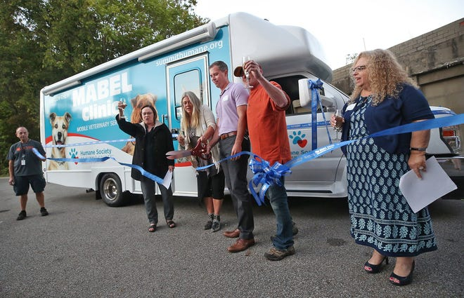 Summit County Humane Society officials cut the ribbon in front of the MABEL Mobile Veterinary Clinic on Tuesday at a dedication ceremony for the van.