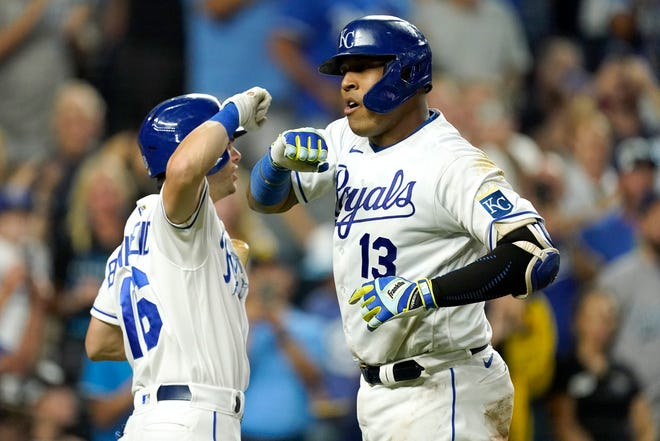 Kansas City Royals' Salvador Perez (13) celebrates with Andrew Benintendi (16) after hitting a solo home run during the sixth inning of the Royals' 6-4 win over Cleveland on Tuesday night. [Charlie Riedel/Associated Press]