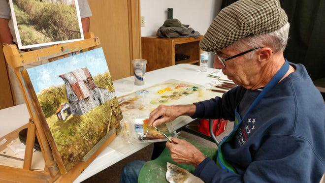 Using a palette knife, Artist Robert Kroeger of Cincinnati paints a barn during a program on his barn-painting at the Mohican Historical Society Friday, Sept. 24.