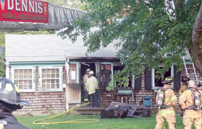 Dennis chief and deputy chief examine the fire scene at 1098 Route 6A in Dennis Wednesday afternoon after it had been mostly extinguished.