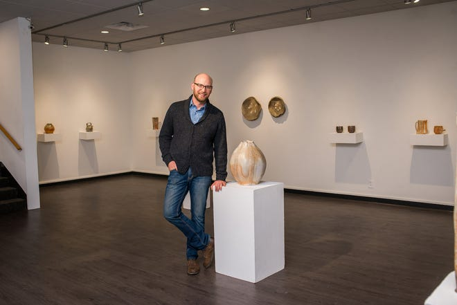 Eric Ordway poses with his work during a 2019 exhibit at the University of Missouri's George Caleb Bingham Gallery. Photo provided by Art + Soul Photography