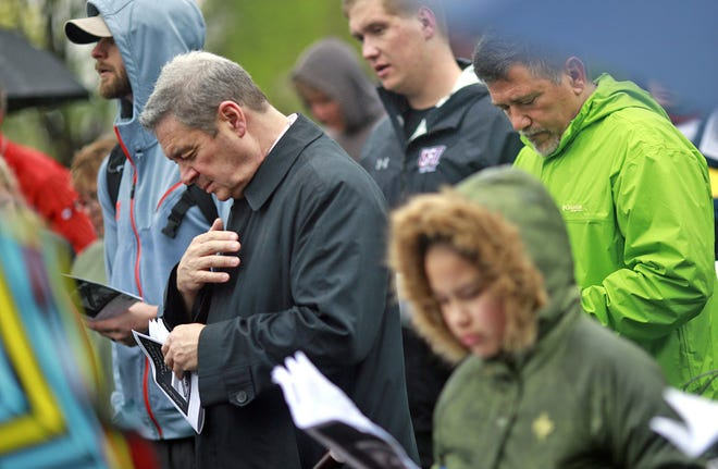 """Columbus Bishop Robert J. Brennan bows his head in prayer at the second station at the Topiary Garden in Columbus, Ohio on April 19, 2019. The event, called """"A Journey Through Peace"""" Walking Stations of the Cross, involved many local churches reciting prayer at each station and reflecting on Jesus's suffering at 14 locations along the three mile route."""