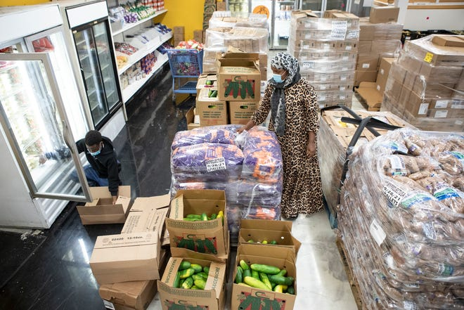 As they prepare to open the Mid-Ohio Market inside MY Project USA's Youth Empowerment Center in the Hilltop, Abdi Yerrow and Sahra Isaak sort through pallets of food donated by the Mid-Ohio Food Collective Tuesday.