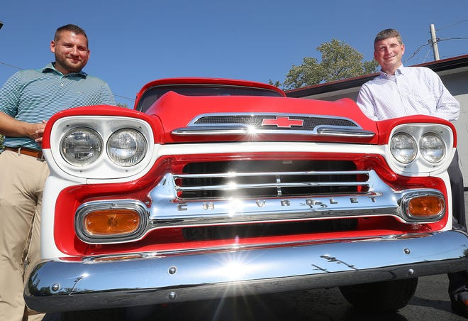 Gahanna Auto Sales general manager Kyle Ballinger (left) and president Craig Leitwein stand next to a 1959 Chevy Apache that is for sale at the lot, 180 Mill St. in Gahanna. Leitwein's father, Steve Leitwein, started the company in 1991.