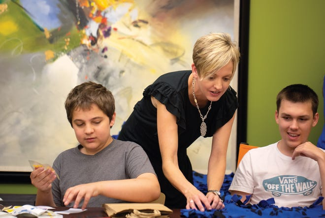 Heather Ohl works with Mason Mattei (left) and Ryan Stephenson as they create puppy starter kits.