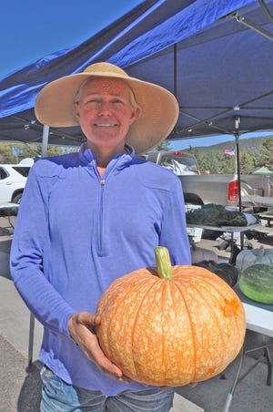 Misty McCullah holds one of her $8 pumpkins. She and her husband Jack own High Plains Farm, which recently moved from Beulah back to the Florence-Penrose area. Lack of labor throughout the economy is adding to the cost of doing business for small farmers like them.