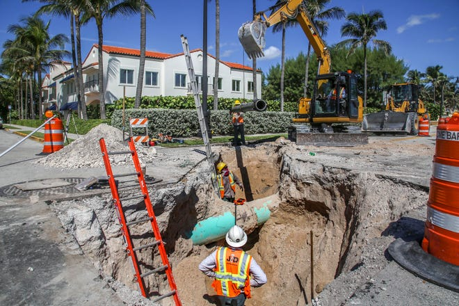 Construction workers install a water pipe at the northwest corner of South Ocean Boulevard and Royal Palm Way on Sept. 27. The project has caused period blocking of traffic.