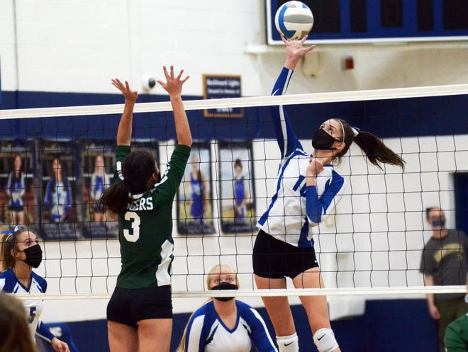 Mackinaw City's Madison Smith (right) gets high above the net for a kill in front of Boyne Falls' Alice Loper during the opening set Tuesday in Mackinaw City.