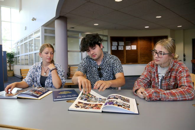 Traip Academy seniors Nora Gilbert, left, Colin Martin and Maggy Johnson look through past yearbooks in the library at the Kittery school as they work on the 2022 edition Wednesday, Sept. 29, 2021.