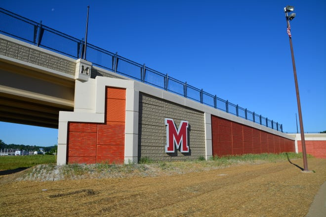 A large M and brick facade connects the Grand Valley Overpass to the city of Martinsville.