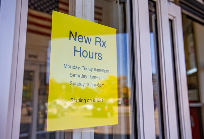 A sign alerting customers to new pharmacy hours is posted at the entrance to a CVS Health in South Bend.