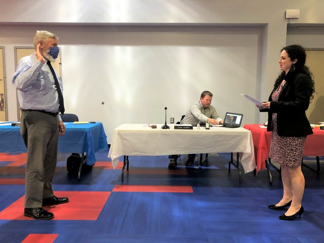New Spencer-Owen Community Schools board member Mark Rogers is sworn in by Christine L. Bartlett, the representative from Ferguson Law Office, the corporation attorney.