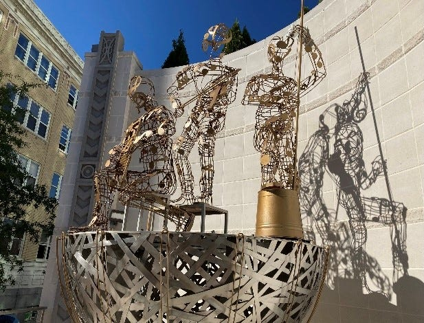 """The """"Ode to Buskers"""" sculpture at the Kimpton Arras Hotel in downtown Asheville has two pieces missing, a small dog and the spoon lady. They should return in October after some minor refurbishment."""
