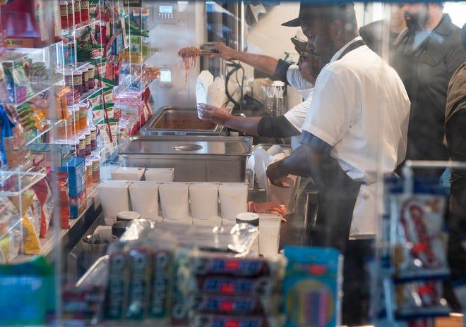 Los trabajadores de la cocina preparan cajas de espaguetis para llevar en la inauguración del restaurante Mom's Spaghetti en Detroit el 29 de septiembre de 2021.
