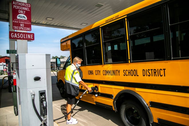 Iowa City school bus driver Dan Ramsey fills up his bus with gas Wednesday. Ramsey is one of a contingent of bus drivers who are seeking hazard pay for transporting children to and from school during the COVID-19 pandemic.
