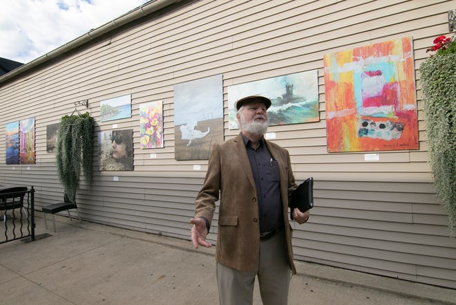 John Wallbank, vice president of the Brighton Art Guild, talks about art Wednesday, Sept. 29, 2021, at Art in the Alley, an outdoor art exhibit on the wall of Brighton Bar & Grill in Hyne Alley.