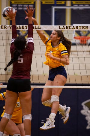Lancaster's Katrina Ventresca (7) spikes the ball over Newark defenders in girls volleyball action at Lancaster High School in Lancaster, Ohio on September 28, 2021.