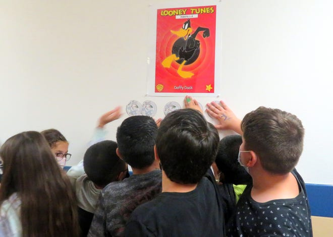 Pictured are fifth-grade students from Kim Perea's Bataan Elementary School class as they place their coins under the 1-5 points Daffy Duck poster.