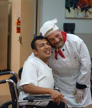 Martin, a longtime client of Desert Arc, enjoys a moment with Mario Del Guidice during one of the pizza-pasta parties hosted at Desert Arc in the past by Mario's Italian Café. Martin loves to get Mario out to dance.