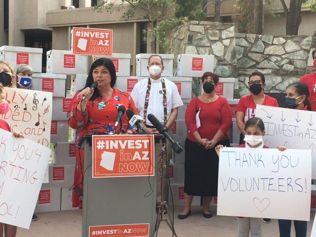 Beth Lewis, director of Save Our Schools, speaks at a rally on Tuesday, Sept. 28, 2021, before delivering thousands of citizen petitions to put Arizona's flat tax on hold until voters can decide in November 2022.